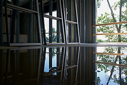 Some of the nature surrounding the site is reflected in a puddle in one of the rooms.