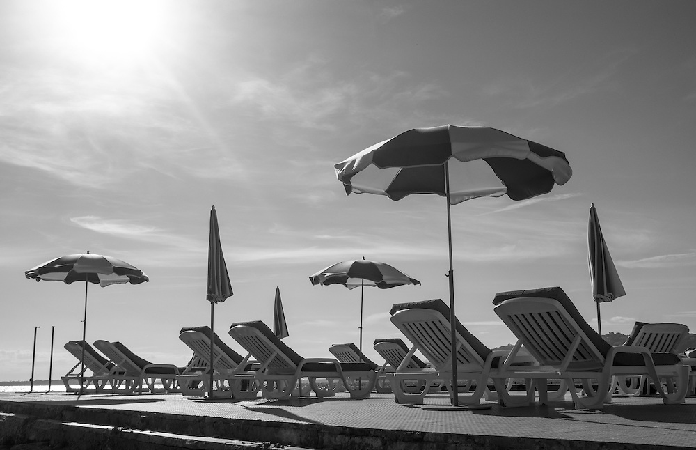 Striped beach umbrellas and chaise lounge deck chairs on a sunny pier on the French Riviera at Juan-les-Pins.