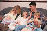 Family group with young girl with Downs Syndrome sitting together on sofa,