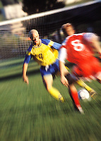 Young men on opposing teams playing soccer at mid field.  Zoom / blur camera effect.<br />