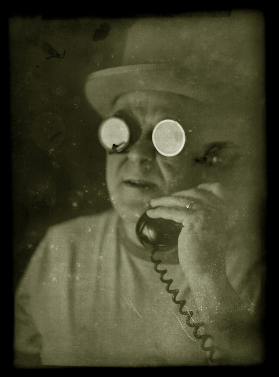A middle aged man wearing strange round glasses and an old hat talking on the telephone.