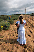 """A pilgrim walks with a vow of silence. The pilgrim route of the Hermandade de Sanlucar de Barrameda from Sanlucar across the Parque Donana to El Rocio, Huelva Province, Andalusia, Spain...El Rocio follows on from Semana Santa - Easter week and the various spring ferias, of which Seville's Feria de Abril (April) is the biggest. The processions to the (Hermitage) Hermita de El Rocío, at Pentecost, is the most famous (Romeria) pilgrimage in the Andalusian region, attracting nearly a million people from across Andalusia, Spain and the world. The cult started off in the 13th century when a statue of the virgin Mary was apparently found in a tree trunk in the Donana Park. What was first a local devotion at Pentecost by local pilgrim brotherhoods """"hermandades"""" became by the 19th century into dozens of fraternities developed from such as Cadiz, Selville and Huelva. Some walk for several days, others travel with oxen drawn wagons or on horseback, with traction engines and all terrain vehicles, camping along the trail they take. They wear Andalusian costumes, tight breeches, boots, short jackets and frilly flamenco skirts. Many festivities, flamenco dance, laments, songs and music are combined with religious prayers. Devout pilgrims walk as a penance, keeping vows of silence. An emblem of the immaculate conception (sin peche) is carried. On the Pentecost after the stroke of midnight on the whit Sunday the virgin Mary is carried from the church through the streets of El Rocio by each hermandade to visit each brotherhood's shrine."""