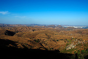 View over barren hills, looking eastwards, towards the White CIty of Udaipur.
