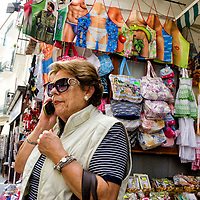 Una señora habla por celular en Amalfi, cerca de una tienda de souvenirs. Costa Amalfitana, Italia. A lady talking on cell in Amalfi, near a souvenir shop. Amalfi Coast, Italy