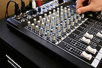 Man adjusting knob on mixing console close-up.