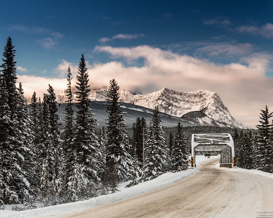A winter scene with Storm Mountain and the Bow River Bridge as seen from Castle Junction in Banff National Park.