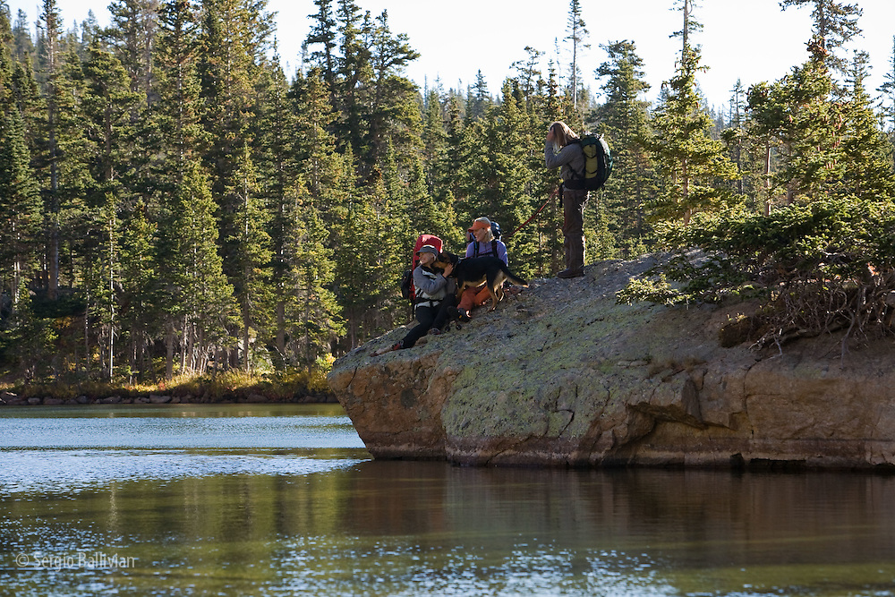 A group of backpackers rest on a rock next to a lake in the backcountry.