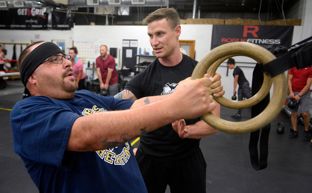 gbs090717b/ASEC -- Jason Torrez, left, stretches with rings, as trainer Barry Ore with Road Runner Fitness gives instructions during  the Addicts2Athlete fitness/therapy program on Thursday, September 7, 2017. They hold the session in the Duke City Strength gym.(Greg Sorber/Albuquerque Journal)