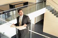 Businessman holding newspaper standing on Mezzanine