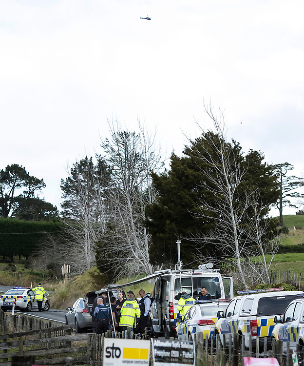 The Eagle helicopter flies overhead as armed police man a road block on Mt Tiger Road after two women were found dead and a man was taken to hospital with gunshot wounds, with the house at the centre of attention now having been engulfed in fire, Whangarei, New Zealand, Wednesday, July 26, 2017. Credit:SMPA / Malcolm Pullman   **NO ARCHIVING**