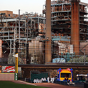 The Bridgeport Harbor Power Station provides a back drop to the ballpark as the Bridgeport Bluefish bull pen wait during the Bridgeport Bluefish V Southern Maryland Blue Crabs, Atlantic League, Minor League ballgame at Harbor Yard Ballpark, Bridgeport, Connecticut, USA. Photo Tim Clayton