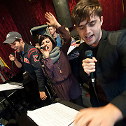 """December 5, 2013 - New York, NY: The cast of the NBC musical drama television series """"Smash"""" including, at microphones in foreground from left, Jeremy Jordan, Krysta Rodriguez, and Andy Mientus, rehearse at Smash Studios at 36th Street in Manhattan on Thursday afternoon in preparation for their cabaret performance of """"HIT LIST,"""" which will premiere Sun, Dec 8 at 54 Below.  Also pictured, in background from left, are Benjamin Rauhala (piano), Eric Michael Krop (vocals), and Shannon Ford (drums). CREDIT: Karsten Moran for The New York Times"""