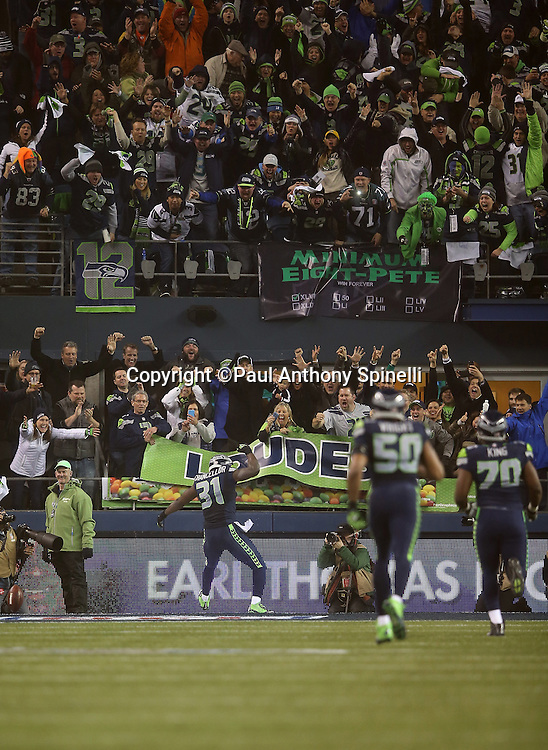 Seattle Seahawks strong safety Kam Chancellor (31) celebrates far down field as fans in the stands join in the celebration after a pick six interception for a touchdown and a late fourth quarter 31-10 lead during the NFL week 19 NFC Divisional Playoff football game against the Carolina Panthers on Saturday, Jan. 10, 2015 in Seattle. The Seahawks won the game 31-17. ©Paul Anthony Spinelli