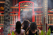 Three women pray while holding incense to their foreheads at Taipei Taiwan's Longshan Temple.