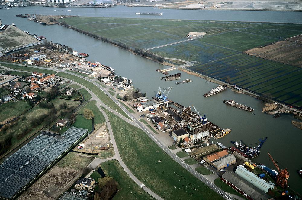 Nederland, Zuid-Holland, Hendrik-Ido-Ambacht, 08-03-2002; metaalindustie (scheepsbouw en -sloop) en overslag zand en grint langs de Veerse Dijk; het eiland, met boven de Noord en onder de Rietbaan is de Sophiapolder; de hiernaar genoemde Sophiaspoortunnel van de Betuweroute loopt diagonaal onder dit gebied door: de betonnen vierkanten (met zand er omheen), rechts vd kassen (linksonder) en midden op het eiland, zijn plaatsen waar de verbinding tussen beiden buizen vd spoortunnel (van boven af) gebouwd zijn; infrastructuur verkeer en vervoer Betuwelijn recycling metalen ruimtegebruik; luchtfoto (toeslag), aerial photo (additional fee)<br /> foto /photo Siebe Swart