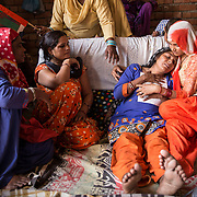 HARYANA, INDIA - MAY, 15, 2017: Relatives console Baed Kaur, 40, (front, second from right) mother of the 22-year-old girl who was gangraped and killed by her jilted lover and his friends, pictured at her residence in the Sonipat area of Haryana, India.<br />