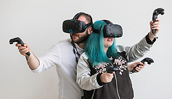 Scotland's first virtual reality arcade. E-VR opens on December 1 at Ocean Terminal, Edinburgh. It offers a variety of virtual reality  (VR) experiences and games. <br /> <br /> Pictured:  Holly Morton VR user with blue hair, Piotr Pyrchala VR user with white t-shirt showcasing an HTC Vive headset.