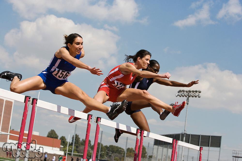 Female athletes hurdling
