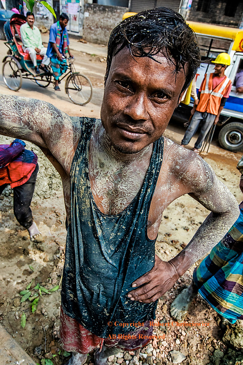 Work Break: A young, mud covered man takes a break from working in a water filled hole, Dhaka Bangladesh.