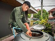 14 JULY 2015 - THAILAND:   A Thai soldiers fills a water tank at a home in Pathum Thani province near Bangkok. The drought that has crippled agriculture in central Thailand is now impacting residential areas near Bangkok. The Thai government is reporting that more than 250,000 homes in the provinces surrounding Bangkok have had their domestic water cut because the canals that supply water to local treatment plants were too low to feed the plants. Local government agencies and the Thai army are trucking water to impacted communities and homes. Roads in the area have started collapsing because of subsidence caused by the retreating waters. Central Thailand is contending with drought. By one estimate, about 80 percent of Thailand's agricultural land is in drought like conditions and farmers have been told to stop planting new acreage of rice, the area's principal cash crop.     PHOTO BY JACK KURTZ