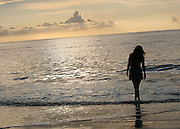 Red head woman silhouette walking in surf at sunrise
