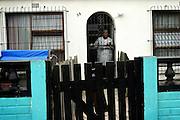 Elisabeth, 62, a woman living in the area of Heideveld, Cape Town, RSA, since about 40 years is scared to go out even during the day because of street gun-fight. She runs a little vegetable shop with her husband, Thomas, 64, in their house. She is portrayed while behind the gate of her house in Heideveld. They acknowledge the fact that thanks to the large police station not far from their house thing are slowly getting better, but also that law enforcement is probably not the right long-term way to curb crime, gangs and drug addiction. They favour development and education for the kids but till now the government of South Africa has promoted a effectual policy towards the area of Heideveld. Police incapacity to control the gang problem has also led to the increase of vigilante groups activity, people that feeling threatened to live in their own community has engaged a fight to the gangs on their own, often creating more hatred and dissent. With extremely high rates of unemployment, poor resources and too little authority control, ghettos as Heideveld are the best places for gangs to grow in activity and businesses. Targeting mostly young people from their area to carry on the 'dirty job', gangs in the Western Cape, and South Africa are an endemic problem in continuous increase in the years after the radical apartheid governmental system. 'Coloured' communities have lost almost all their help from a government that now is concentrated on empowering black communities instead. Segregated into ghettos and without state grants or development activities, people in these community are sometimes forced to join a gang or dealing drugs also to provide for their own family.