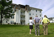 Unidentified residents of Centennial Station Condominiums survey the damage to one of the fire damaged buildings at the complex, Sunday, July 23, 2000, in Warminster, Pa. A three alarm fire, which started in a storage closet, caused fire and smoke damage to the third and fourth floor, and water damage to the lower floors. MANDATORY CREDIT:(William Thomas Cain/photojournalist.cc)