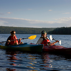 Two young women kayak on Lake Francis in Pittsburg, New Hampshire.