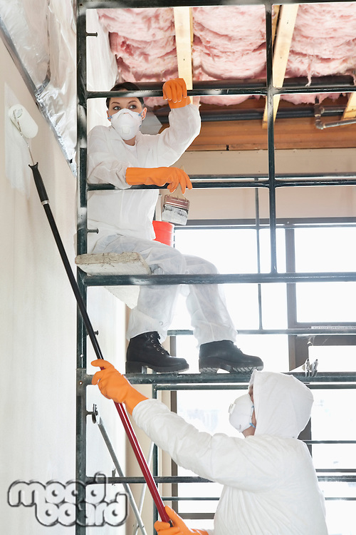 Two construction workers on scaffold painting a room