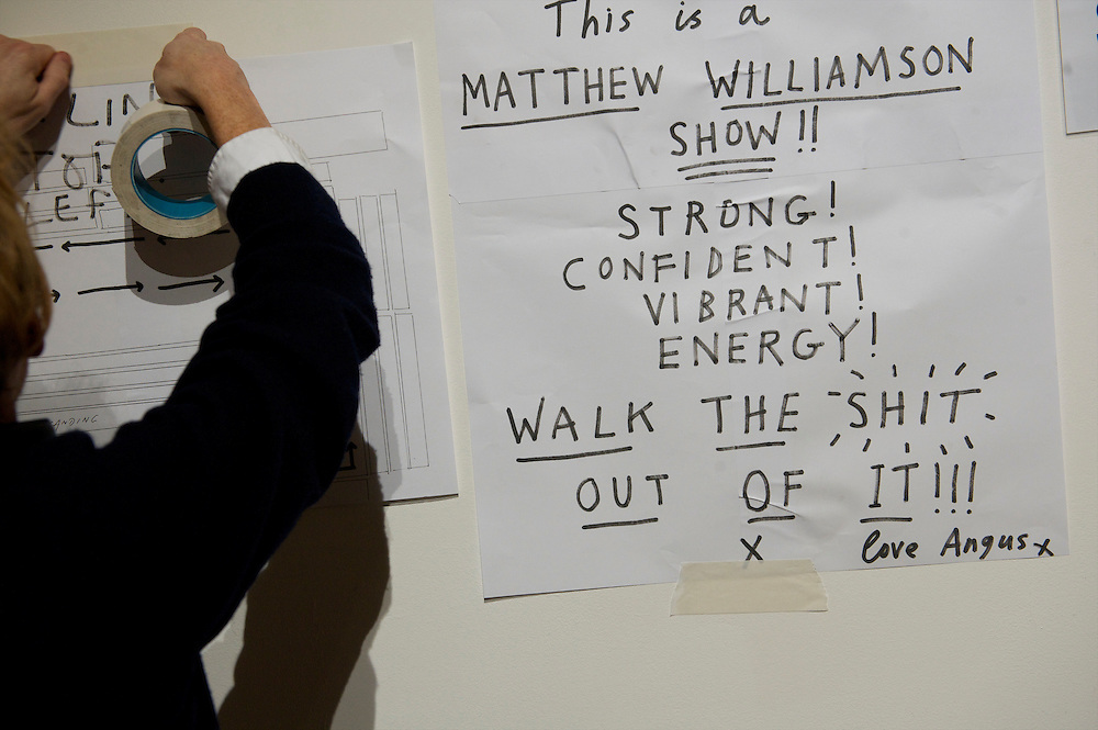 A fashion show producer pastes inspirational messages on the wall next to the backstage catwalk entrance before the Matthew Williamson autumn 2011 collection at Phillips de Pury Gallery in London on 20 February 2011.