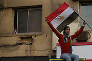 A young girl wearing a surgical mask to protect herelf from tear gas is seen in a window in Tahrir Square in Cairo , Egypt November 23,2011.  (Photo by Heidi Levine/Sipa Press).