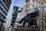 A conservator with City of London contractor Rupert Harris Conservation, uses a pressure jet spray to hose off the statue of Victorian philanthropist, entrepreneur and banker George Peabody (1795 to 1869). As part of a rolling programme of maintenance and cleaning by the Square Mile's governing Corporation, historic items - from statues and plaques to other pieces of historic value are regularly attended to.