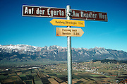 Mountain top footpath sign post above a Liechtenstein valley with the town of Nendeln below.