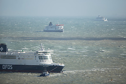 © Licensed to London News Pictures. 26/04/2016. DFDS Dover Seaways vessel needs help from a tug while in the harbour. High winds from Storm Doris cause problems at The Port of Dover. Ferries struggle to berth and more ferries are left to wait in the channel while the port is closed. Photo credit: Martin Apps/LNP