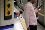 female person scrubbing the yellow for the blind tile strip Japan