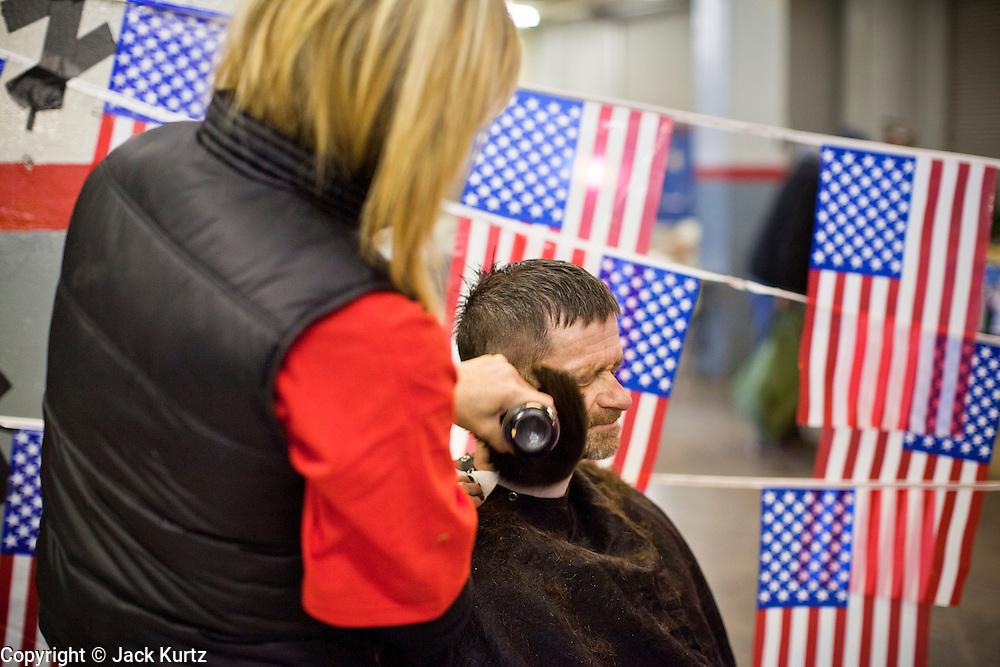 04 FEBRUARY 2011 - PHOENIX, AZ: DALE SPARKS, a homeless veteran of the US Army gets his haircut at the Arizona StandDown Friday. The Arizona StandDown is an annualthree day event that brings together theValley's homeless and at-risk militaryveterans, connecting themwith services ranging from: VA HealthCare, mental health services, clothing, meals, emergency shelter, transitional and permanent housing,ID/ drivers license's, court services and Legal Aide, showers, haircuts and myriad other services and resources. Arizona StandDown isheld annually at theVeterans Memorial Coliseum at the Arizona State Fairgrounds in Phoenixon Super Bowl weekend.    Photo by Jack Kurtz