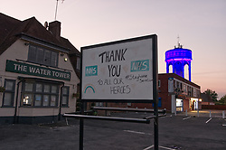 To honour NHS and care workers water treatment firm APS in conjunction with Thames Water (owners) and Stanley Electronics lit up tower. Shot from The Water Tower Pub, now closed, who made the Thank You sign. Coronavirus lockdown, Tilehurst UK 2020