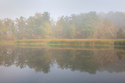 The first hints of autumn color are visible through fog over Kendall Lake in Cuyahoga Valley National Park, Ohio.