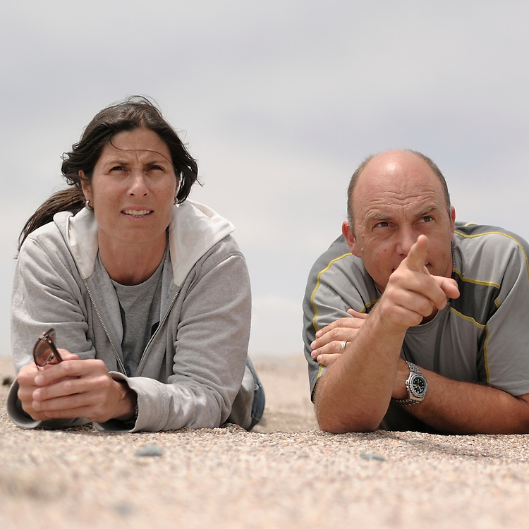 [M] (digital composite of two images) from the left to right Dr. Ingrid Wiesel (Brown Hyena Research Project), Solvin Zankl (Photographer), on the lookout for the brown hyena.
