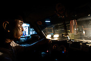 A taxi driver with a mouthful of beetlenut maneuvers through the streets of Yangon, Myanmar.