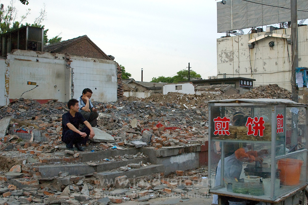 China, Beijing, Chaoyang, San Jian Fang, 2008. Life goes on as usual after demolition teams armed only with sledgehammers reduced this corner to rubble..