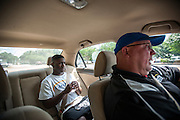 "BEAUFORT, SC - JULY 14: CJ Cummings and his weightlifting coach Ray Jones discuss the 14-year-old's weight before competition during the car ride to practice on July 14, 2014 in Beaufort, South Carolina. A former U.S. Olympic coach has called Cummings ""the best weightlifter this country has ever seen."" (Photo by Stephen B. Morton for The Washington Post)"