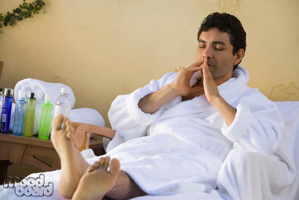 Man in bathrobe, relaxing outdoors
