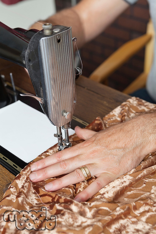 Male tailor stitching cloth on sewing machine