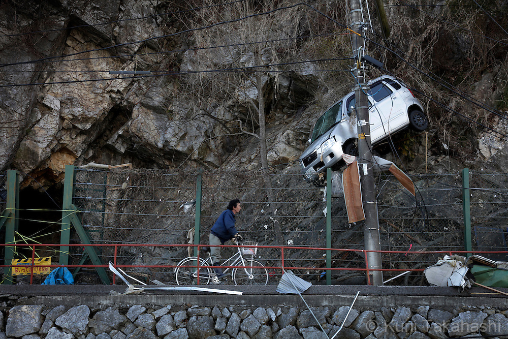 A man rides bicycle under a car which washed away in Kesennuma, Miyagi, Japan after on March 27, 2011, after massive earthquake and tsunami hit northern Japan. More than 20,000 were killed by the disaster on March 11.<br /> Photo by Kuni Takahashi