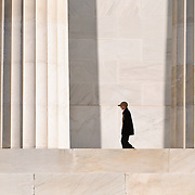 A teenage boy visiting the Lincoln Memorial is dwarfed by the massive marble columns.