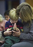 Diane Cahill and her son, Robert Brown 3, pray together during a worship service at The New Life Community Church which meets in the gymnasium/cafeteria of the Elk Grove Elementary School.  The startup church's  minister is Richard Christenson  and each Sunday morning he and other church members prepare for the 10am service, setting up chairs, sound and visual equipment.  This Sunday, February 3, 2002 nearly 70 adults and children attended the service.