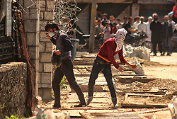April 27, 2018 - Srinagar, Jammu and Kashmir, India - A protester throw stones towards Indian police in old city Srinagar. Minor clashes erupted in old city after the prayers ended in Jamia Masjid (Grand mosque) ,the protesting youth shouted pro freedom slogans and demanded justice for the 8-year old girl who was raped and murdered in Jammu's Kathua district in January 2018. (Credit Image: © Faisal Khan via ZUMA Wire)