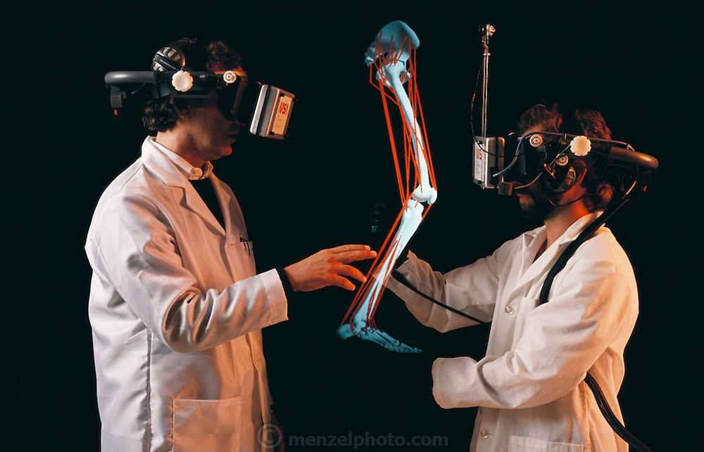 Applications of virtual reality systems in medical education. Here, Scott Delp and Scott Fisher are using a system developed at NASA's Ames Research Centre in Menlo Park, California, to study the anatomy of the human leg. They both wear a headset equipped with 3-D video displays to view the computer-generated graphical images - one is shown between the two doctors. Physical exploration of the leg anatomy is afforded by using the data glove, a black rubber glove with woven optical fiber sensors, which relays data on their physical hand movements back to the computer. Model Released (1990)