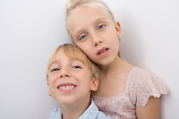 Portrait of brother and sister over gray background